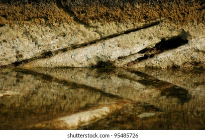 Stone texture of an ancient natural rock with reflection in the water