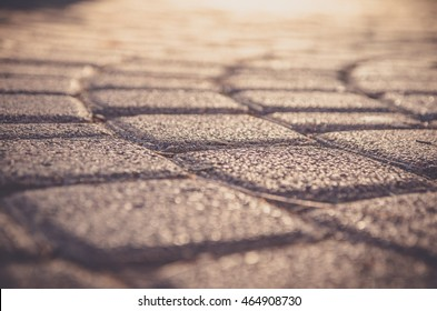 stone texture, selective focus, paving stone with sunlight cobblestone stone at sunset, warm paving stone, warm cobblestone, detailed stone, close up pavement