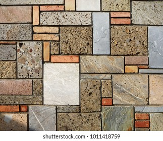 Stone texture. Wall with bricks and  blocks of polished stones of various colors and sizes,  geometrically arranged