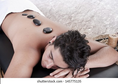 Stone therapy. Man getting a hot stone massage at spa salon