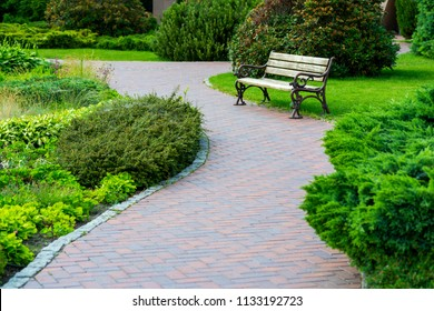 A stone tile path with a wooden seat in a green park with a landscape design