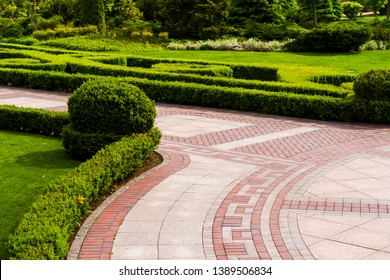 stone tile walkway with green bushes in landscape design
