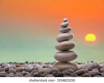Stone tower on the beach. Background is blurred sundown