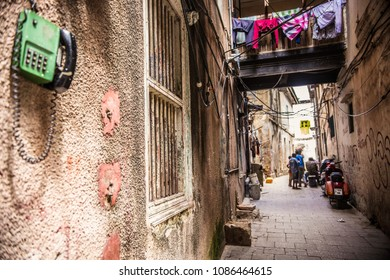 STONE TOWN, TANZANIA - January 2018: Traditional house at Stone Town, Zanzibar. Old house courtyard, people outside and phone on the wall, Tanzania