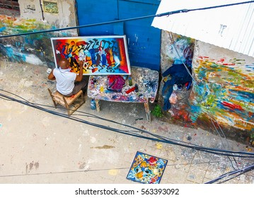 STONE TOWN, TANZANIA - SEPTEMBER 23, 2010: Local African artist works on colorful African paintings in outdoor workshop in Stone Town, Zanzibar.