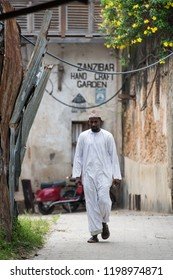 Stone town, Zanzibar - 8 December 2017: Man in muslim wear and skullcap walking along the street after praying in  mosque