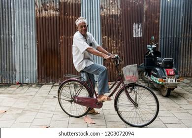 Stone town, Zanzibar - 8 December 2017: Happy old man riding a bicycle in a street of Stone town, Zanzibar