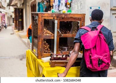 STONE TOWN, ZANZIBAR - January 2018: African man selling dry dates on the narrow street of Old Stone town at Zanzibar, Tanzania