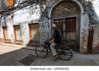 STONE TOWN, ZANZIBAR - JANUARY 9, 2015: Unidentified cycler on Stone Town street