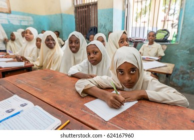 STONE TOWN, ZANZIBAR, TANZANIA CIRCA MARCH 2017, School girls and school boys smiling at camera in the class room.Wide angle and motion blur