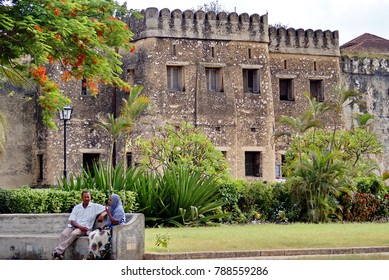 STONE TOWN, ZANZIBAR, TANZANIA - CIRCA JANUARY 2014: Couple on a park bench in front of the fort