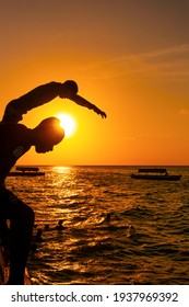 Stone Town, Zanzibar, Tanzania - January 2020: Locals run and jump into the sea From Stone Embarkment at Sunset time