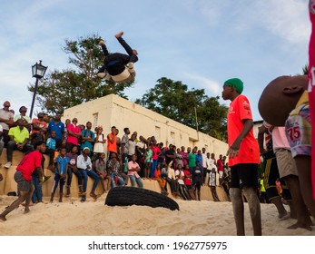 Stone Town, Zanzibar, Tanzania - January 2021: Crowds of people watch like young people jump on an inner tube on a sandy beach in Stone Town. Africa