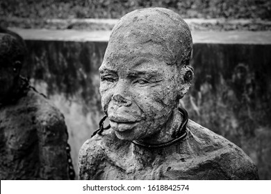 Stone Town, Zanzibar, Tanzania, Jul 08, 2016: Monument to slaves near former slave trade market. Sculpture of slave near Anglican Cathedral Church of Christ in Stone Town, Zanzibar. Black and white