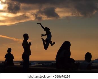 Stone Town, Zanzibar, Tanzania - November 25, 2015: Locals run and jump into the sea in Zanzibar as the sun sets.