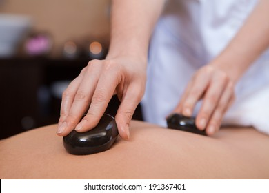 Stone treatment. Woman getting a hot stone massage at a day spa