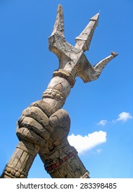 A stone trident with sky and clouds