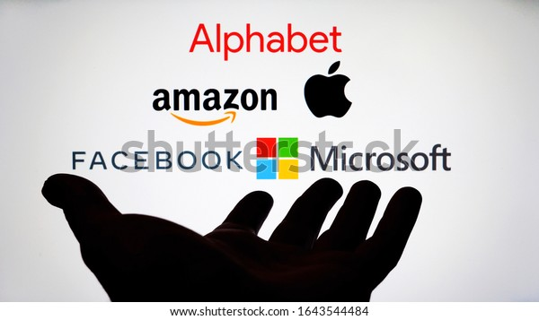 Stone / UK - February 12 2020: Big Five companies. Big Tech company logos: Alphabet, Amazon, Apple, Facebook, Microsoft on a screen and a silhouette of hand. Not a montage. Digital tax, antitrust.