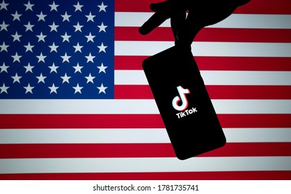 Stone / UK - July 22 2020: TikTok ban America. TikTok logo seen on the silhouette of smartphone hold in a hand with American flag on the back. US Banned Tik Tok concept. Not a montage.