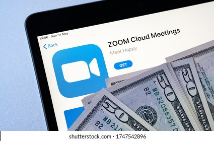 Stone /UK - May 28 2020: Zoom Cloud Meetings app in Apple app store seen on iPad screen and dollar bills placed on top. Concept for Zoom revenue and share price.