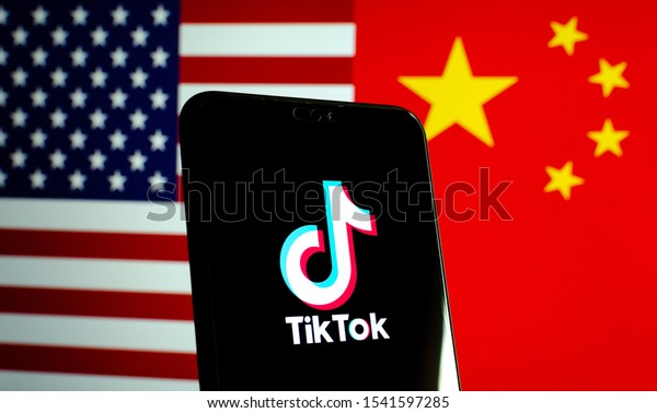 Stone / UK - October 25 2019: TikTok app logo on a smartphone screen and flags of China and United States. Tiktok WeChat are banned. Apps are in centre of US - China tensions and security concerns.