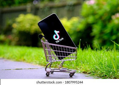 Stone / UK - September 3 2020: TikTok logo on the smartphone placed in a miniature shopping trolley. TikTok sale and acquisition by Microsoft, Oracle or Walmart. Concept.