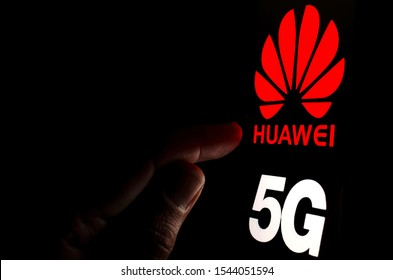 Stone / United Kingdom - October 16 2019: Huawei 5G logo on a smartphone screen in a dark room and a finger pointing at it.  Concept.