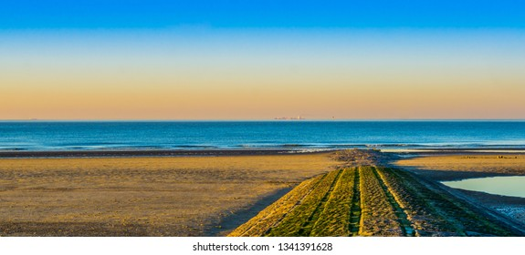 stone walking path of rocks leading to the sea, beautiful beach at sunset in Blankenberge, Belgium.