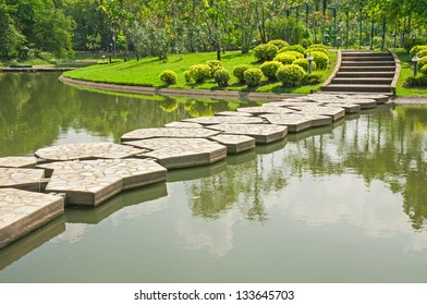 stone walkway across water in the park
