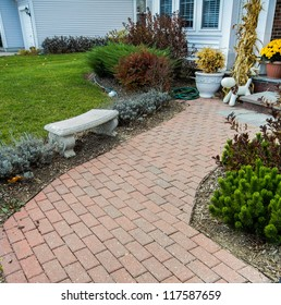 Stone walkway leading to driveway and footpath wth lush green grass lawn and flowerbed