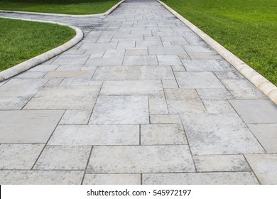 Stone walkway In The Park. Empty Sandstone Path Among Grass.