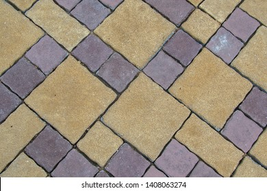 Stone walkway with square flagstones of different colors & size. Diagonal arrangement.