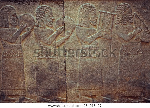Stone wall with ancient musicians, who is playing on antique musical instruments. Relief with assyrian musical scene - art and culture of Mesopotamia and Babylonia, Istanbul museum.