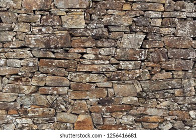 Stone wall background. Ancient wall of dry masonry. Stone wall texture in the historic city of Santiago de Compostela