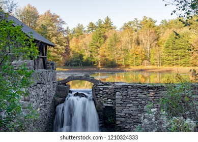 Stone wall and building with waterfall and Autumn trees reflected on Lake in upstate New York.