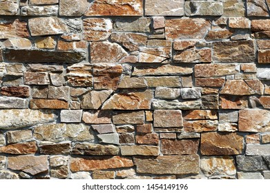 Stone wall cladding made of  brown and gray natural rocks. Background and texture