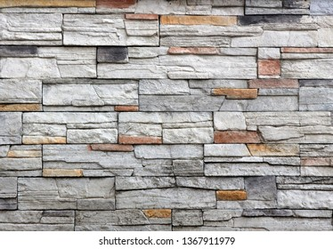 Stone wall cladding made of gray rock mixed with red and black stripes