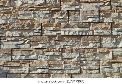 Stone wall cladding made of stacked irregular and horizontal rock strips,  under sunlight . Colors are white and light brown.