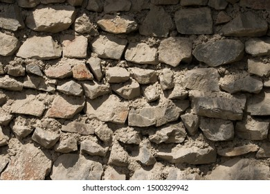 Stone wall close up. Part of a stone wall, for background . Texture of thick and strong wall of rough stones of various shapes and sizes.