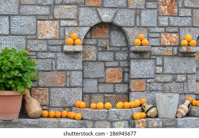 Stone wall decorated with yellow oranges and cretan vases