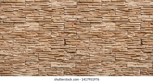 Stone wall detail with natural worked rocks of different shapes and colors,Seamless Bricks Stone wall elevation for Abstract backgrounds.