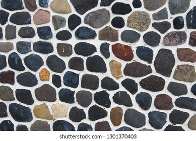 Stone wall of a greek house in Santorini, natural rocks laid carefully in neat mosaic pattern