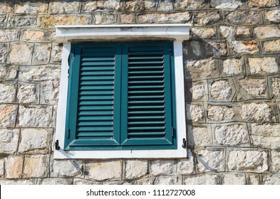 Stone wall house with wooden shutters on the windows.  Meditteranean architecture style.