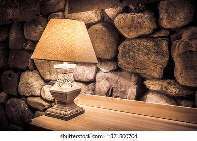 Stone wall illuminated by stylish lamp on wooden table