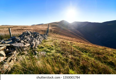 A stone wall leading up the mountain ridge towards Ladyside Pike and Hopegill Head on a sunny day in the English Lake District, UK.