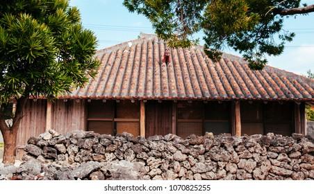 Stone wall and Okinawa local wooden clay roof house in historic Ryukyu village in Taketomi, Okinawa, Japan
