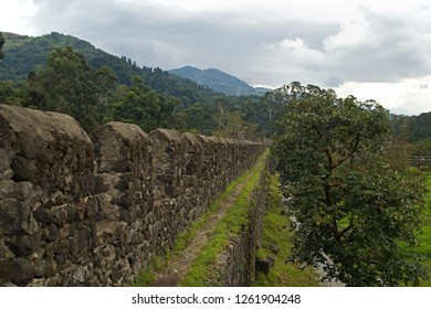 Stone wall of the old Roman fortress with loopholes and a path on it. Behind the stney is a high hill completely overgrown with dense forest. The sky is gray and gloomy. Georgia