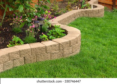 stone wall with perfect grass landscaping in garden with artificial grass