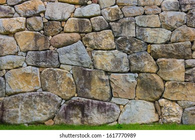 Stone wall, reliable foundation. Rough rough stone, cobblestones of various shapes and sizes, antique masonry. Below is green grass.