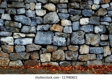 A stone wall and sidewalk with autumn leaves